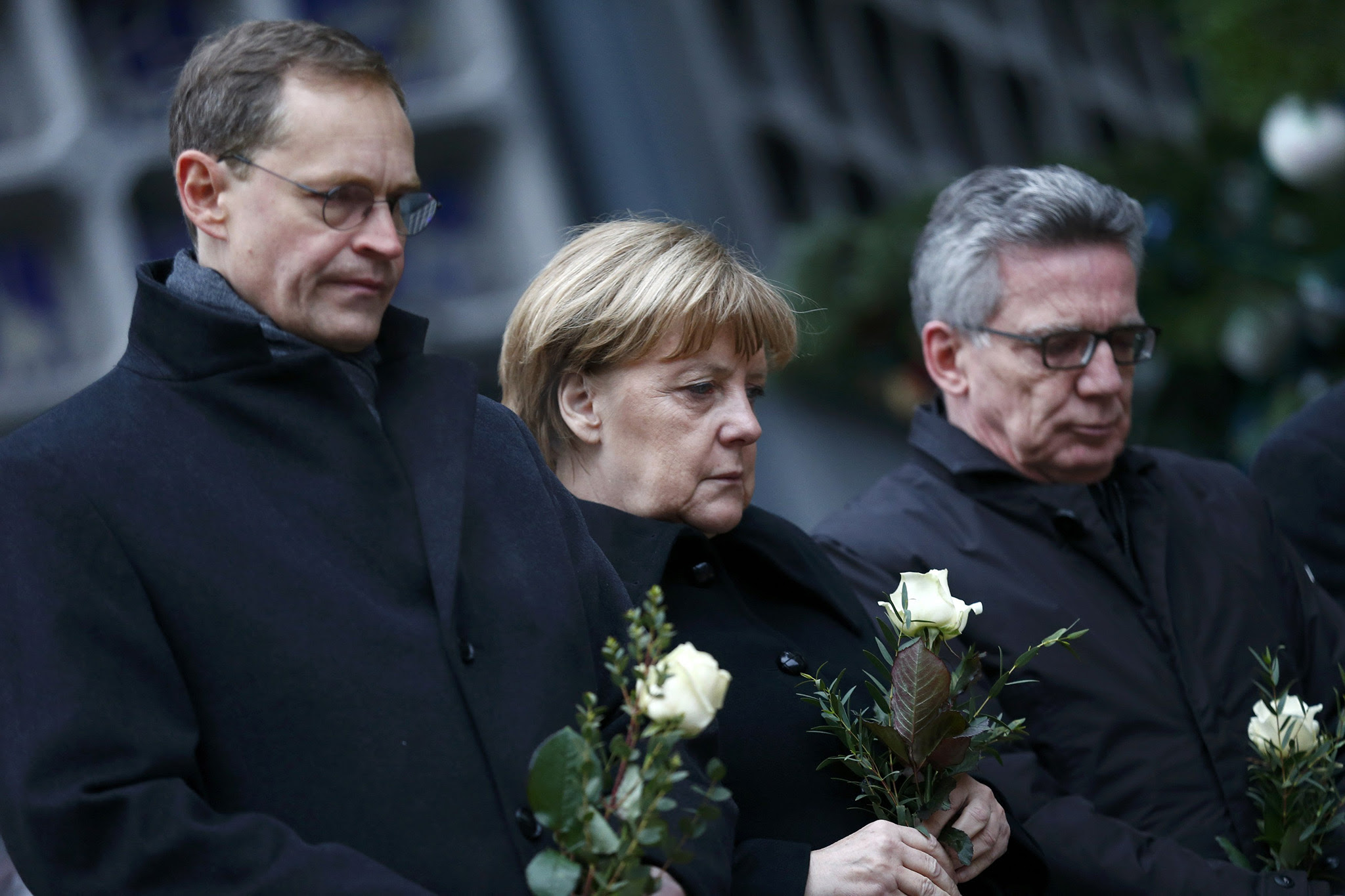 Berlin mayor Michael Mueller, German Chancellor Angela Merkel and German interior minister Thomas de Maiziere stand in silence at the Christmas market in Berlin, Germany, December 20, 2016, one day after a truck ploughed into a crowded Christmas market in the German capital.
