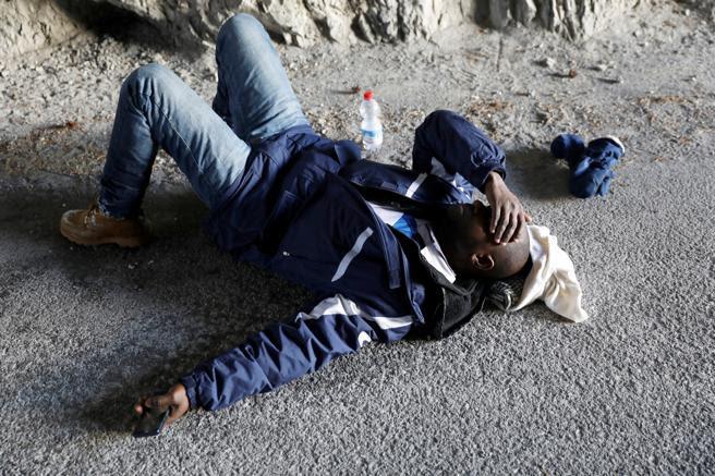Abdullhai, de 38 años, de Guinea, descansa después de cruzar parte de la cordillera de los Alpes