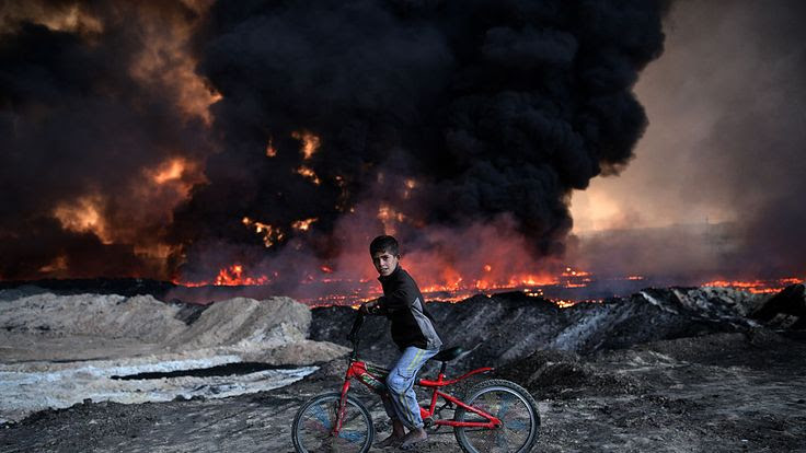 A boy rides his bike past an oil field set on fire by retreating IS fighters