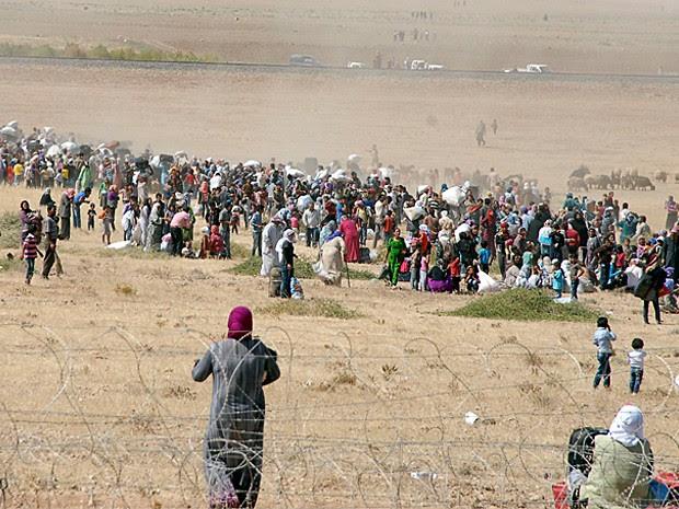 Curdos cruzam a fronteria da Síria com a Turquia em fuga contra a ação do Estado Islâmico (Foto: Stringer/Reuters)