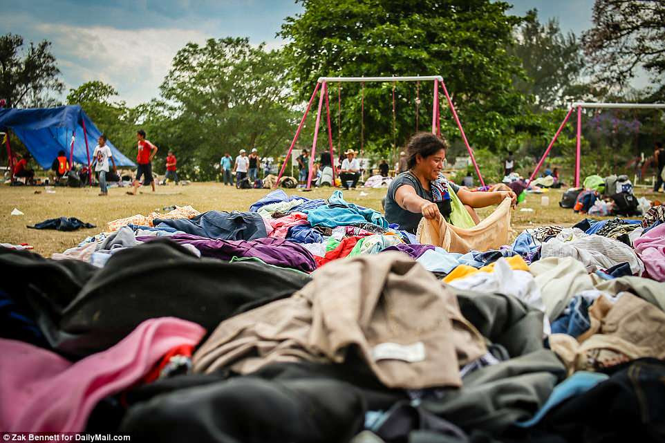 A migrant woman, traveling with the Pueblo Sin Fronteras group, sifts through donated clothes at the Ferrocarrilero VÌctor F. Morales Sports Center