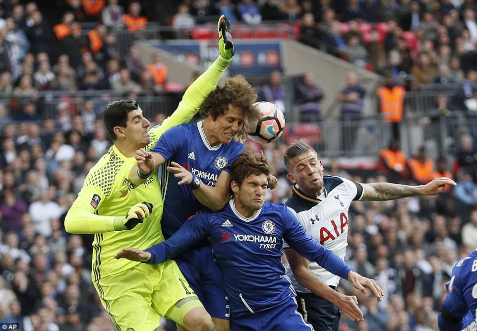 Chelsea goalkeeper Thibaut Courtois smashes into team-mates Luiz and Marcos Alonso as he tries to clear the ball