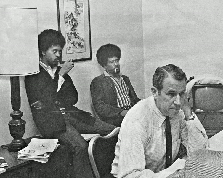 Description of  NOV 5 1969 - Two men, one identified as a member of the Black Panthers Colorado chapter, sit behind Western Athletic Conference Commissioner Wiles Hallock after an interruption of the WAC meeting Wednesday at Cosmopolitan Hotel. The meeting later was recessed. (Millard D. Smith/The Denver Post)