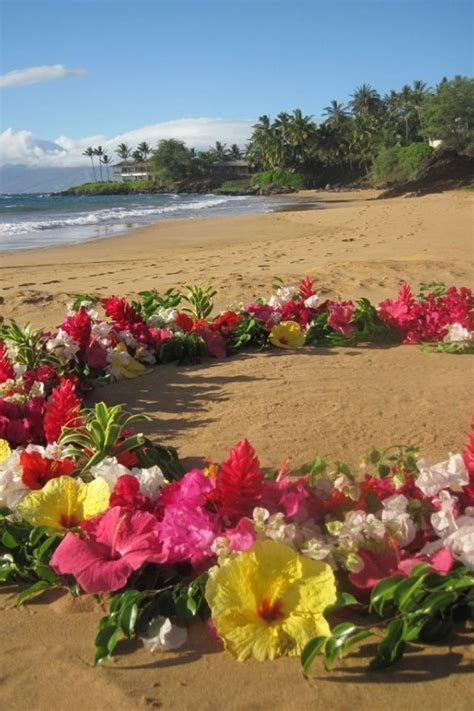 Tropical flowers form a sacred ceremony space on the beach