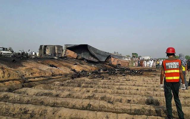 Socorrista observa corpos queimados depois que um caminhão-tanque sofreu acidente e pegou fogo no Paquistão (Foto: STR / AFP Photo