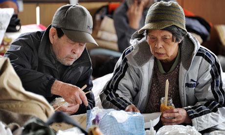 People eat at an evacuation centre in Ishinomaki, Miyagi prefecture