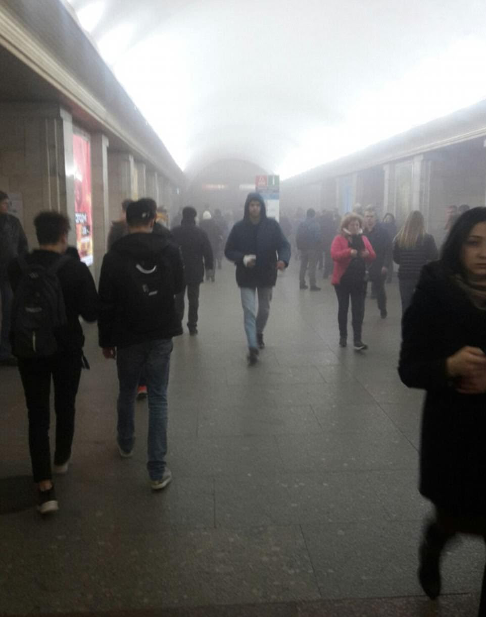 Commuters walk away from the carnage as smoke fills the station in St Petersburg, Russia