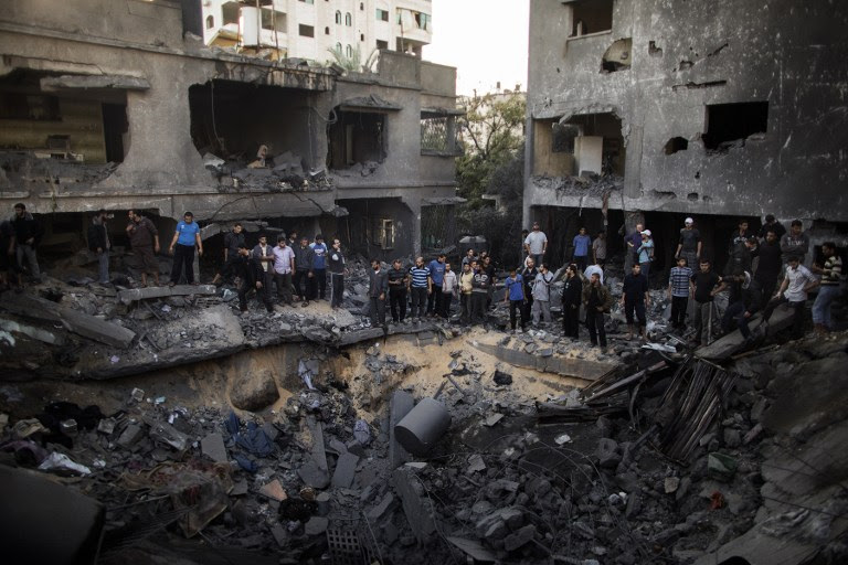 AFTERMATH. Palestinian men gather around a crater caused by an Israeli air strike on the al-Dallu family's home in Gaza City on November 18, 2012. AFP PHOTO/MARCO LONGARI