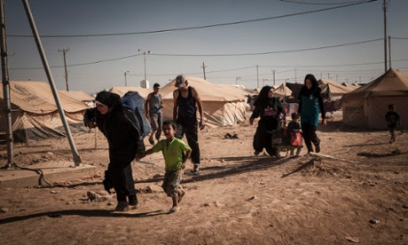 Syrian refugees carry their belongings to their tent after arriving at the Zaatari refugee camp in Jordan.