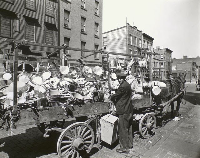 Travelling tin shop, Brooklyn. Tinker looks over his shoulder at camera while he ties box to wagon already loaded with pans, brushes, basins, etc.