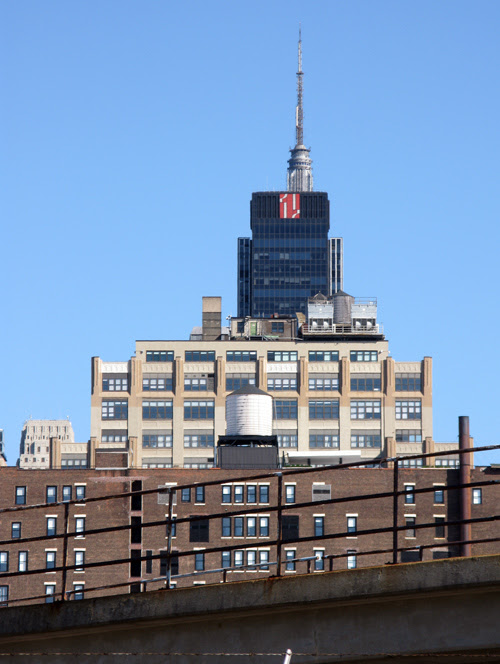 the tops of several buildings create one big building, including the top of the Empire State Building, Manhattan, NYC