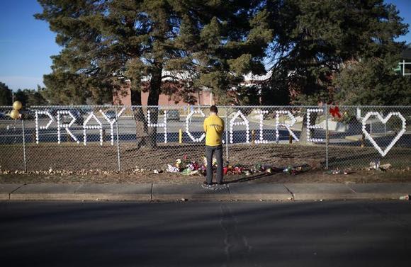 An Arapahoe high school student prays at the school in Centennial, Colorado December 15, 2013. REUTERS/Rick Wilking