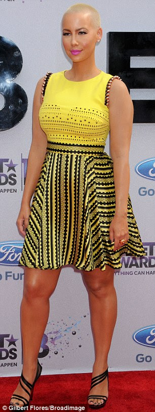 Like a bumble bee: Amber donned a black-and-yellow frock with studded shoulders