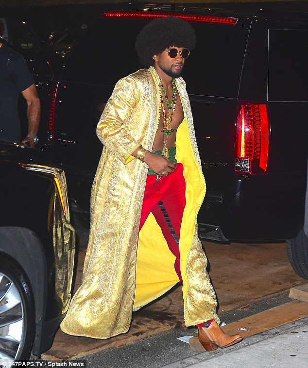 Cool dude: Usher looked seriously slick in an open gold coat, worn with red trousers