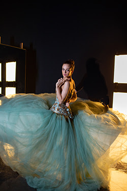 photo of principal dancer captured in twirling motion in a tulle blue green gown