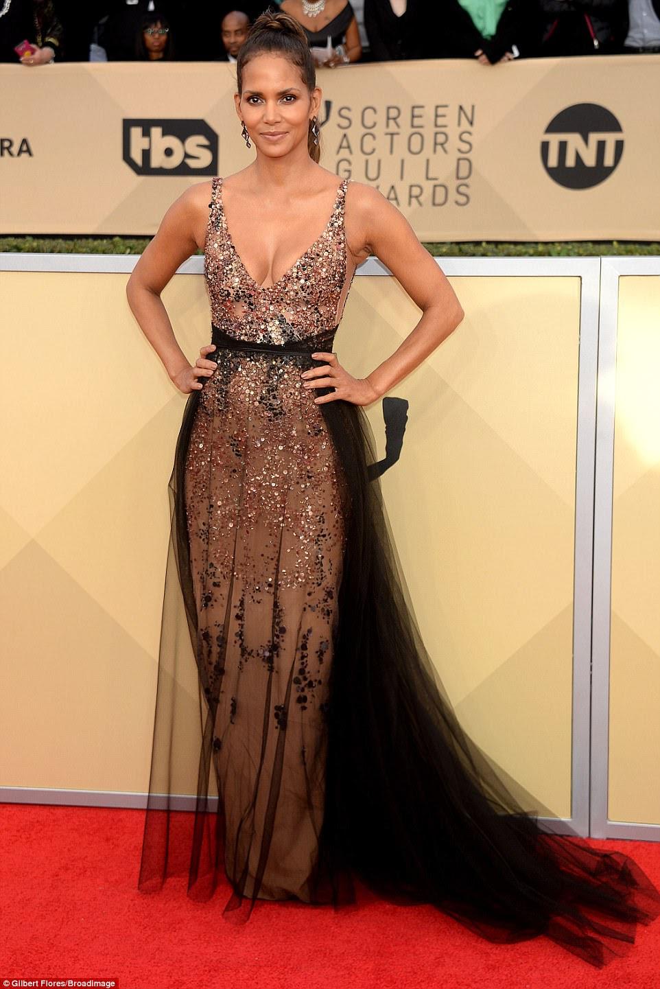 Deusa: Halle, de 51 anos, escolheu um vestido de lantejoulas de bronze com uma saia de sobreposição de renda preta;  a estrela de cinema emparelhou o vestido dramático com os cabelos traseiros puxados e o batom nu