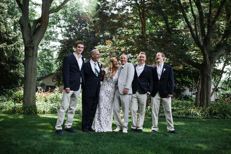 Formals  portraits with a bride and groom, father of the bride, and sons following a small backyard wedding ceremony in Rockford IL. Photo by Mindy Joy Photography