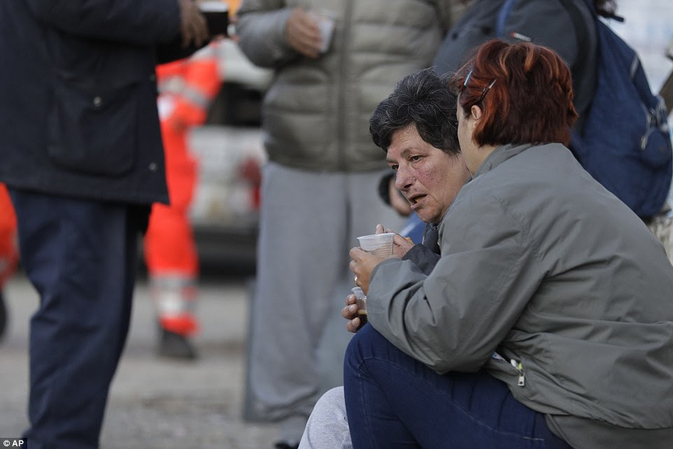 Shocked and scared people drink water in a tent camp near Pescara Del Tronto on Thursday morning as aftershocks continued to be felt in the area