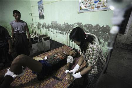 A man injured in the recent sectarian violence is treated by a nurse at a hospital in Kyuktaw township October 25, 2012. REUTERS-Soe Zeya Tun