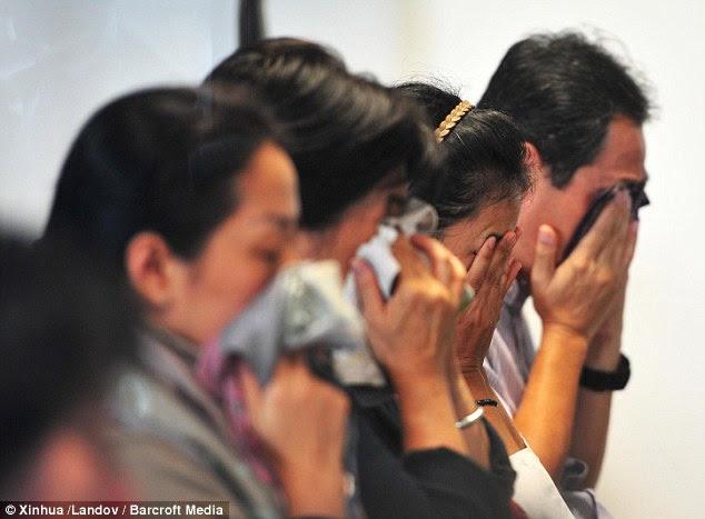 Family members of people on Air Asia flight QZ8501 pray together at Juanda International Airport