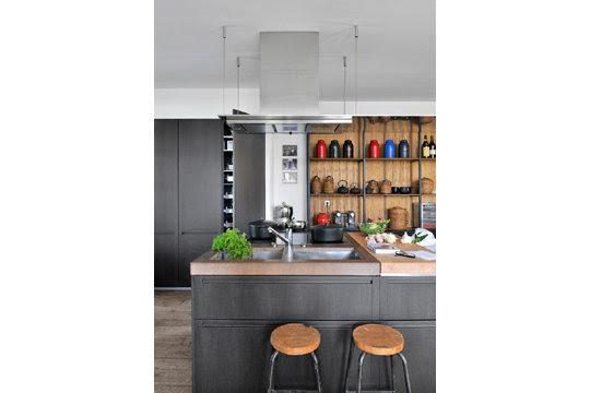 La cuisine Boffi en chêne et pierre noire regarde la vue.
