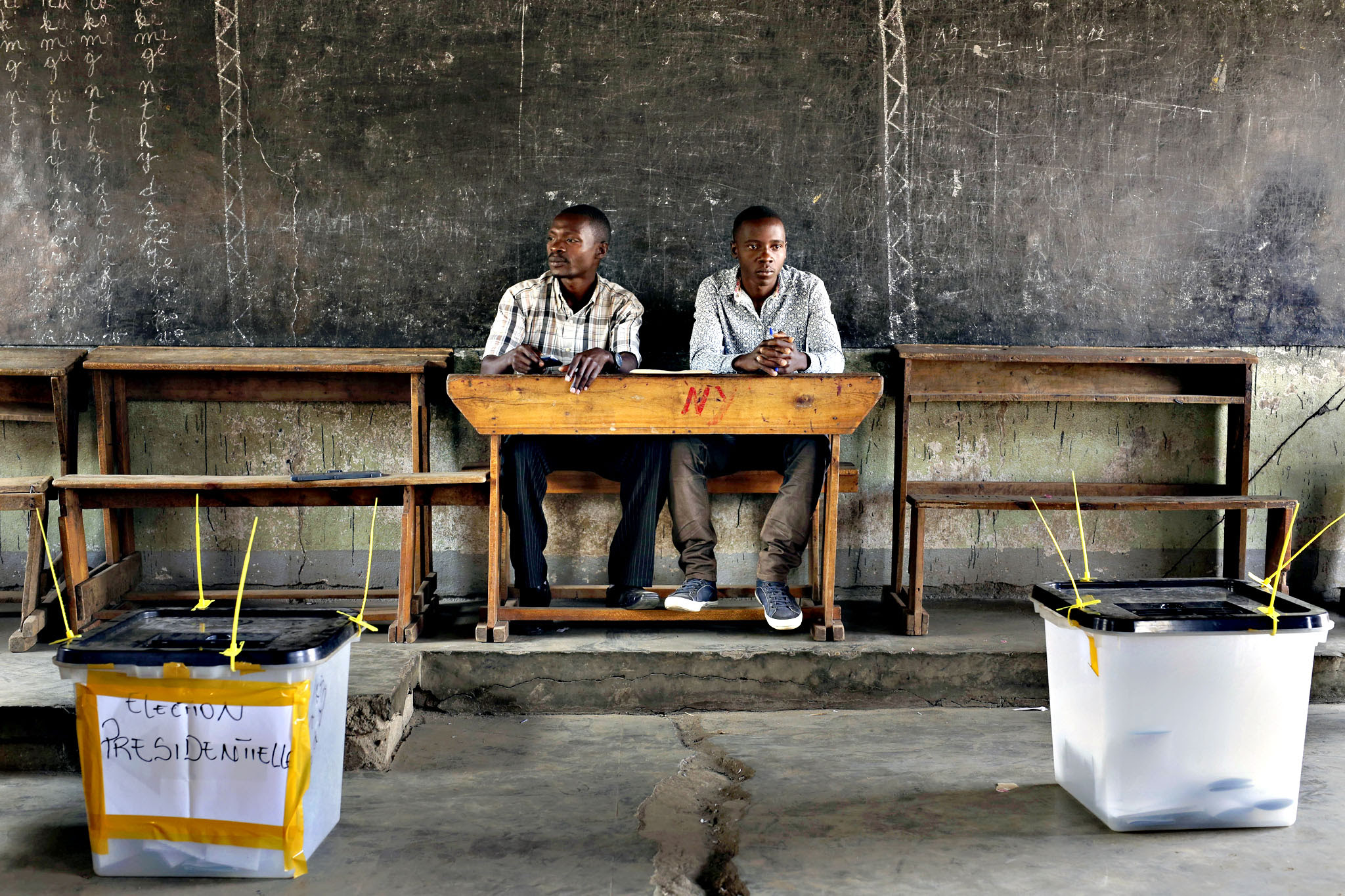 Election observers sit in an empty polling station for the presidential elections in Bujumbura, Burundi, Tuesday, July 21, 2015. A low turnout was experienced in several polling stations in the Burundi s capital at the start of voting in the country s presidential election following a night of explosions and gunfire in at least two opposition strongholds that oppose President Pierre Nkurunziza s candidacy for a third term in office