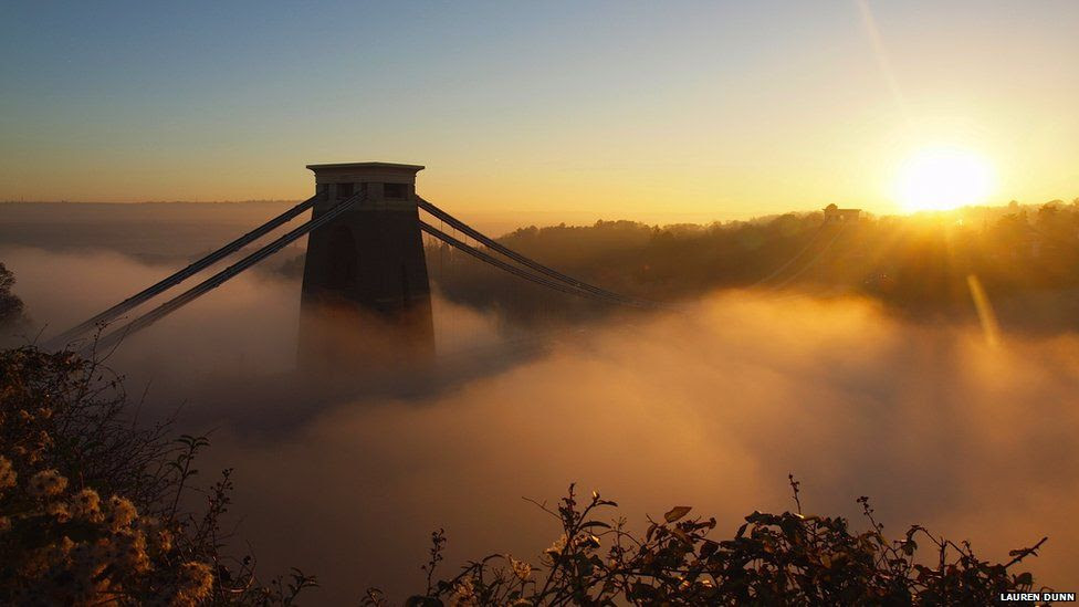 A suspension bridge is almost completely shrouded in mist at sunset