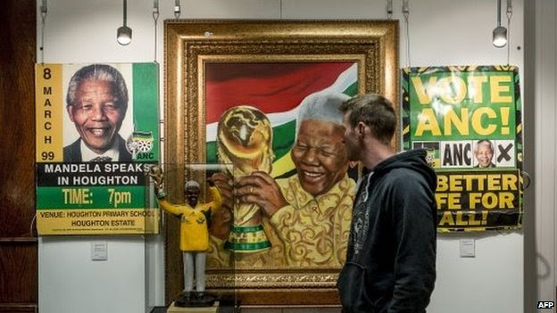 A man looks at a portrait of late South African President Nelson Mandela on July 15, 2014