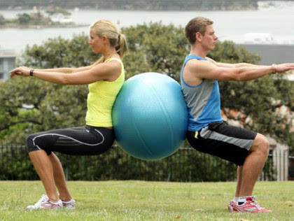 3. Swiss ball partner squats