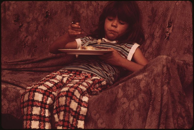 File:DIANE WATKINS, ONE OF NINE CHILDREN OF A MULKY SQUARE FAMILY EATS ON THE LIVING ROOM COUCH. THE ONLY TABLE IN THE... - NARA - 553524.jpg