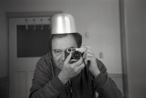 reflected self-portrait with Olympus-35 ECR camera and metal hat by pho-Tony