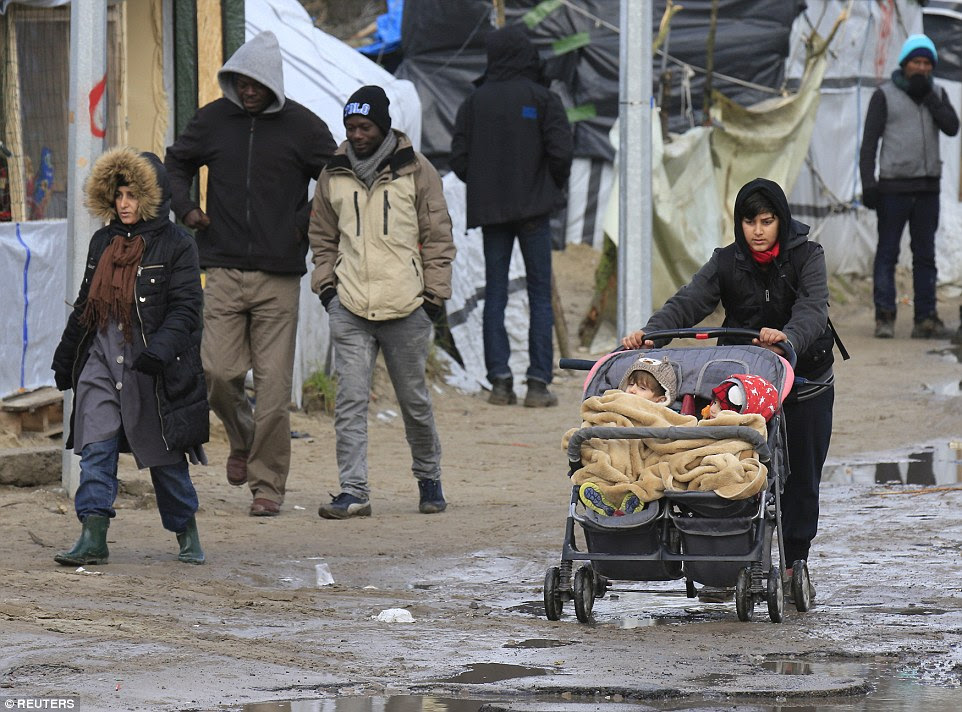 A Kurdish migrant pushes a pram with her children through a muddy area in the southern part of the Jungle