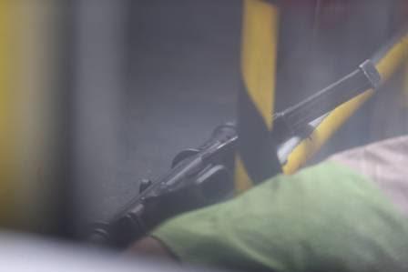 A metralhadora, ao lado do corpo do suspeito
