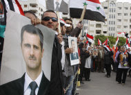 Pro-Syrian regime protesters, hold portraits of Syrian President Bashar Assad and shout slogans against the Arab League, as they gather outside the Syrian foreign ministry where Syrian Foreign Minister Walid al-Moallem helds a press conference, in Damascus, Syria, on Monday Nov. 14, 2011. Syria's foreign minister accused Arab states on Monday of conspiring against Damascus after the Arab League voted to suspend Syria's membership over the government's deadly crackdown on an eight month-old uprising. (AP Photo/Muzaffar Salman)