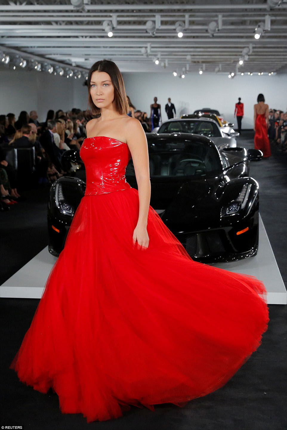 Red hot: Bella Hadid also stepped onto the runway for the iconic American designer, dressed in a floor-length gown
