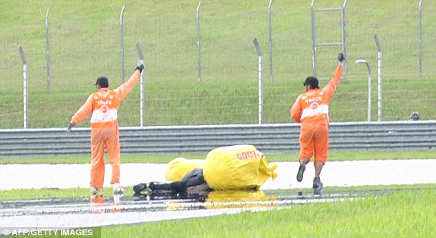 Tragedy: Race marshalls attend to Honda rider Simoncelli (C) following his fatal crash just four minutes after the start of the Malaysian MotoGP race