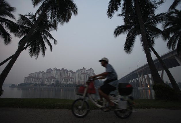 Man rides past hazy skyline of Tanjong Rhu residential area in Singapore