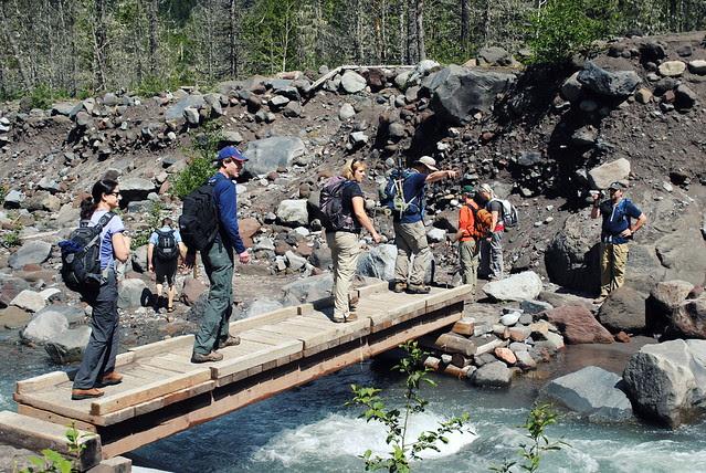 Hikers crossing the seasonal bridge - Ramona Falls Trail - Mt Hood
