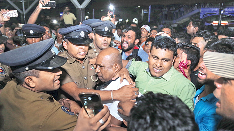 Police trying to calm down irate train commuters at the Colombo Fort Railway station, who were stranded as a result of the train strike last evening. Picture by Rukmal Gamage