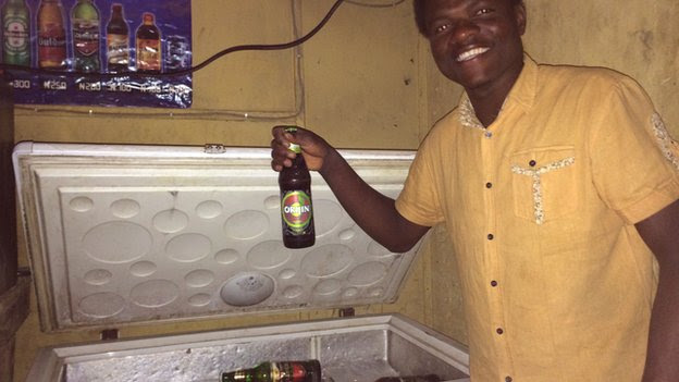 Bar tender Paul Bini in Kano holding a beer