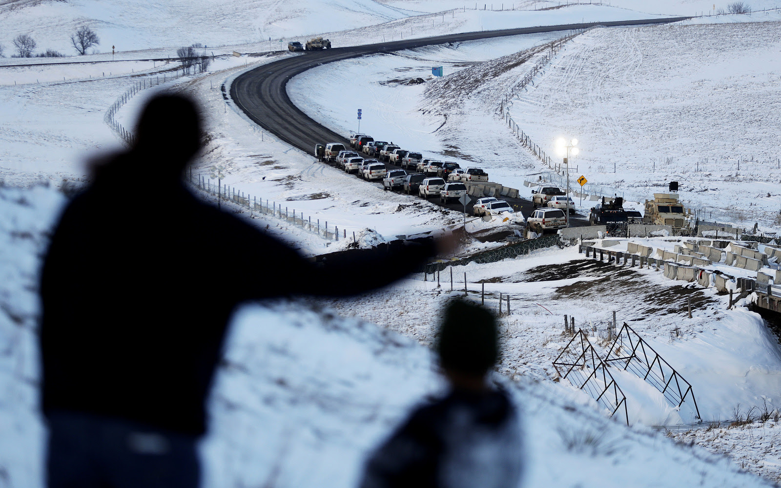 Law enforcement vehicles line a road leading to a blocked bridge next to the Oceti Sakowin camp where people have gathered to protest the Dakota Access oil pipeline in Cannon Ball, N.D. (AP/David Goldman)