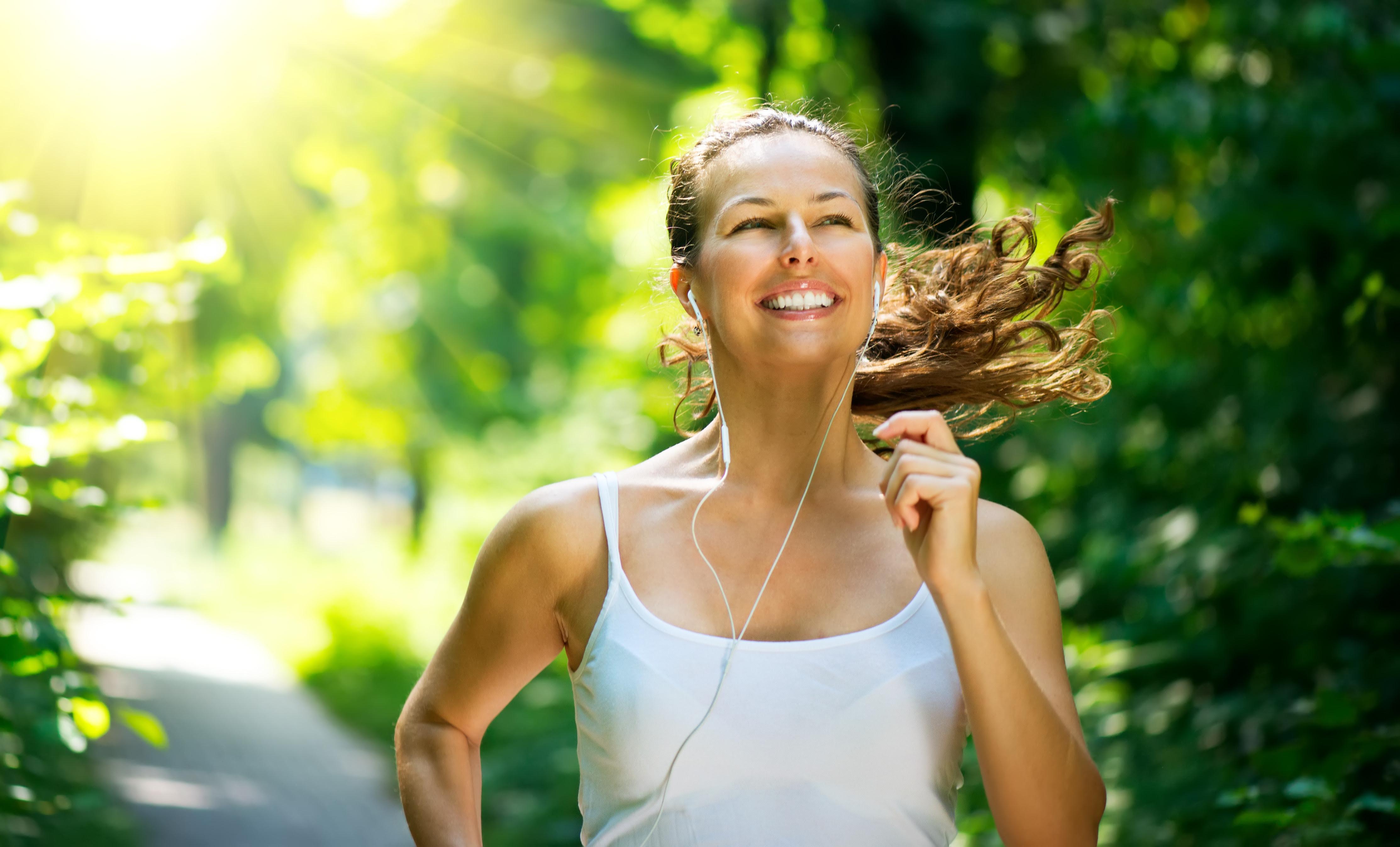 Mulher sorridente, com fones de ouvido, praticando corrida