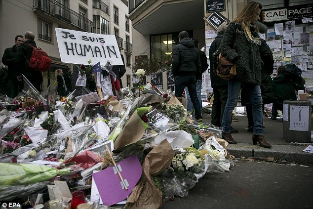 Defiant: The new cover of Charlie Hebdo centres on an image of the Prophet Muhammad, who is weeping and holding a sign which declares: 'Je Suis Charlie'. Pictured, floral tributes outside the offices in Paris