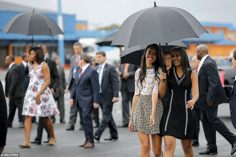 Obama's daughters Malia and Sasha beamed as they sheltered under an umbrella at Havana's airport after arriving in Cuba on Sunday
