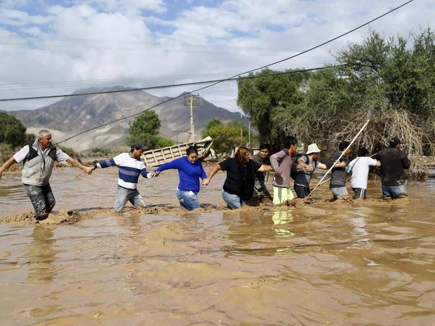 Moradores atravessam um rio inundado em Copiapo, no Chile. O número de mortos no país subiu para quatro após chuvas castigaram o norte (Foto: Ivan Alvarado/Reuters)