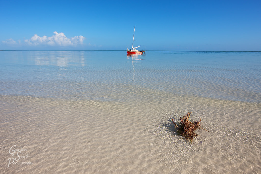 Red Sailboat clear caribbean waters