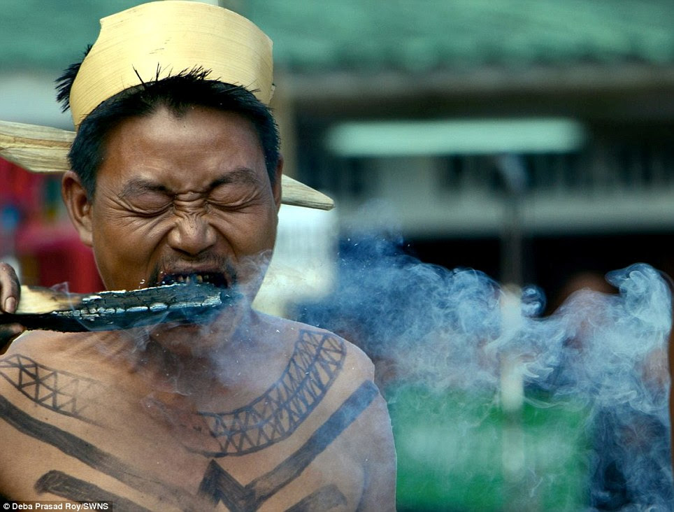 A fire eater in Kohima, Nagaland, India, tenses up as he bites into a burning stick