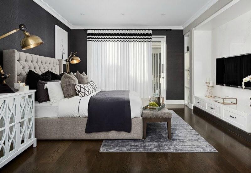 hamptons style master bedroom with tufted headboard and dark floor