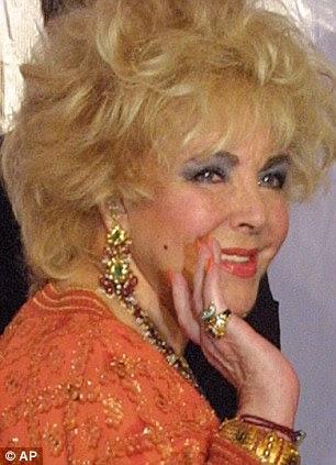 Ela acena para a imprensa na casa de leilões Christie em 2002, como algumas de suas posses são vendidos