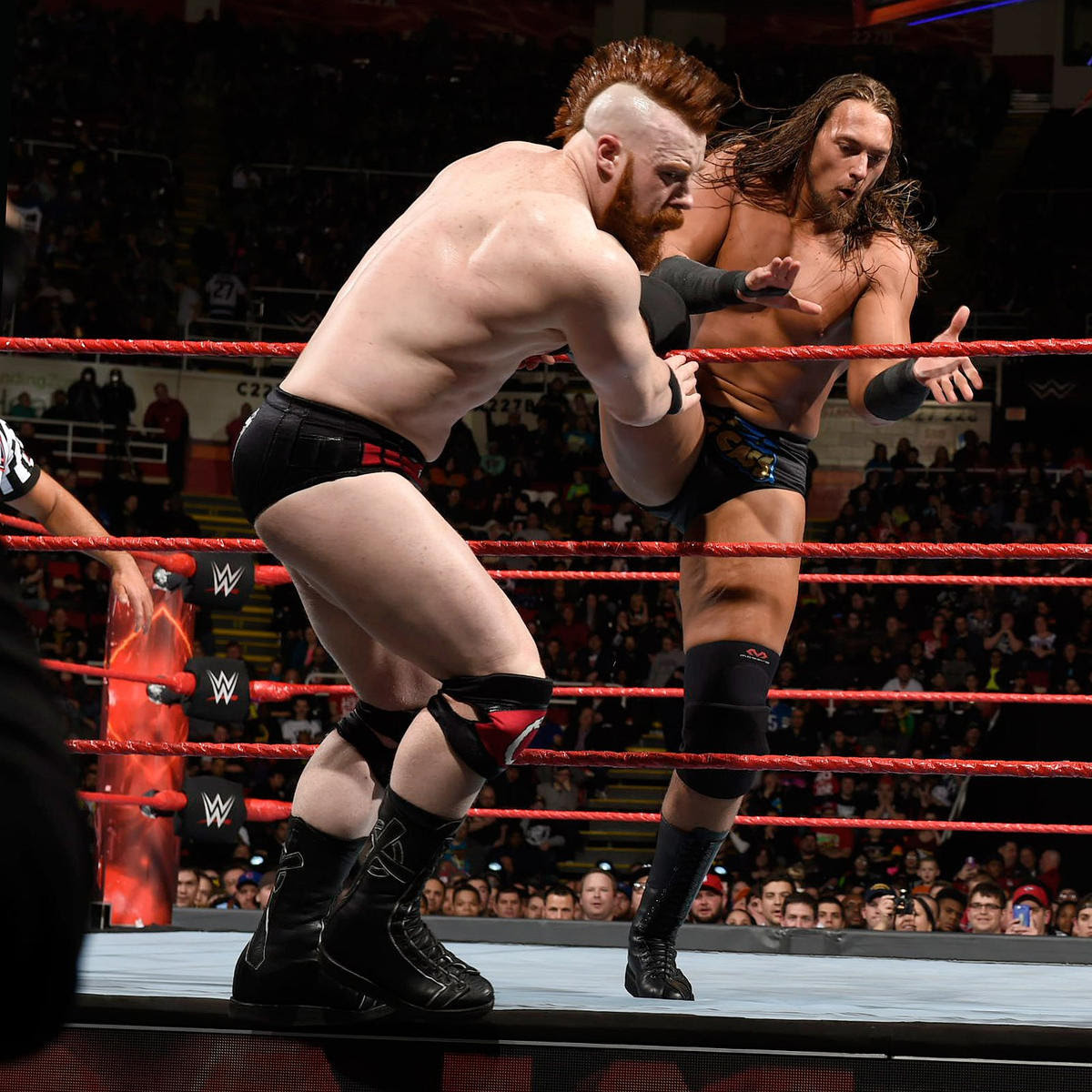 Big Cass attempts to kick Sheamus off the ring apron.
